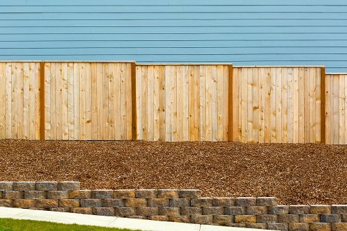 New Garden Wood Fence with house siding and barkdust mulch with concrete retaining wall along exterior sidewalk